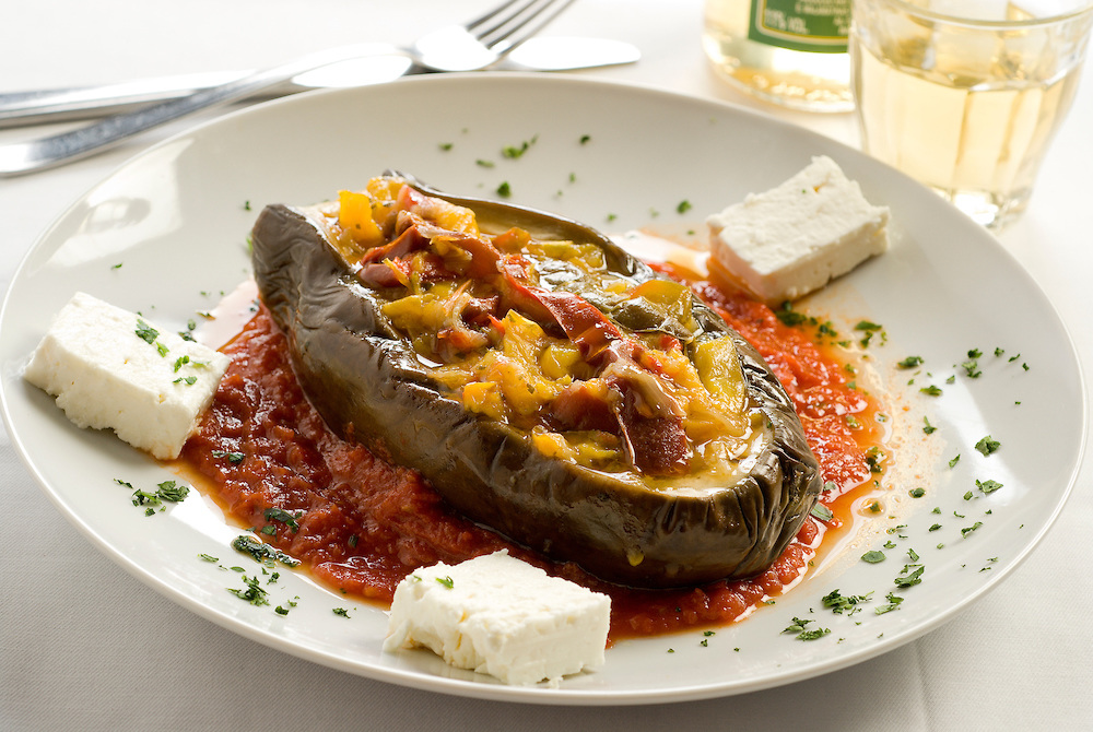 imam baildi, stuffed and stewed eggplant served with tomato sauce and feta cheese and persil
