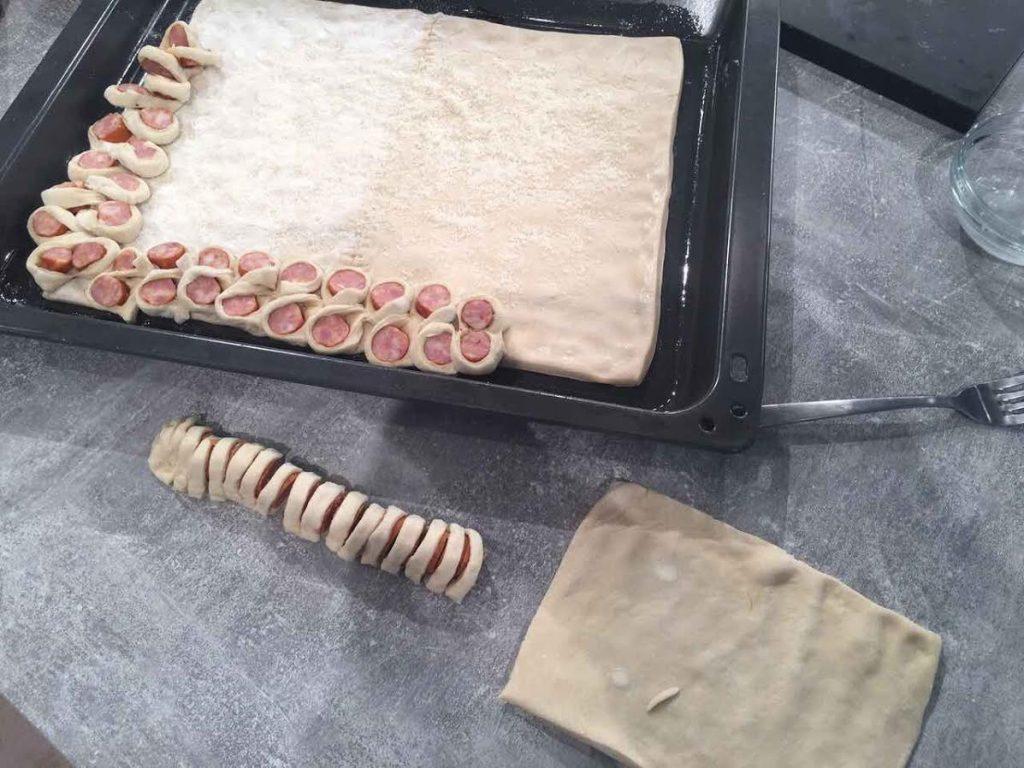 Παίρνουμε τα άλλα δύο φύλλα ζύμης, τα κόβουμε σε φαρδιές λωρίδες και τυλίγουμε τα λουκάνικα. Με κοφτερό μαχαίρι τα χαράζουμε σε λεπτές φέτες, όχι μέχρι κάτω, και τα «κολλάμε» περιμετρικά στην πίτσα, ενώνοντας τη ζύμη της πίτσας με τη ζύμη του τυλιγμένου λουκάνικου. Έτσι, σχηματίζονται δαχτυλίδια λουκάνικου, γύρω από την πίτσα.