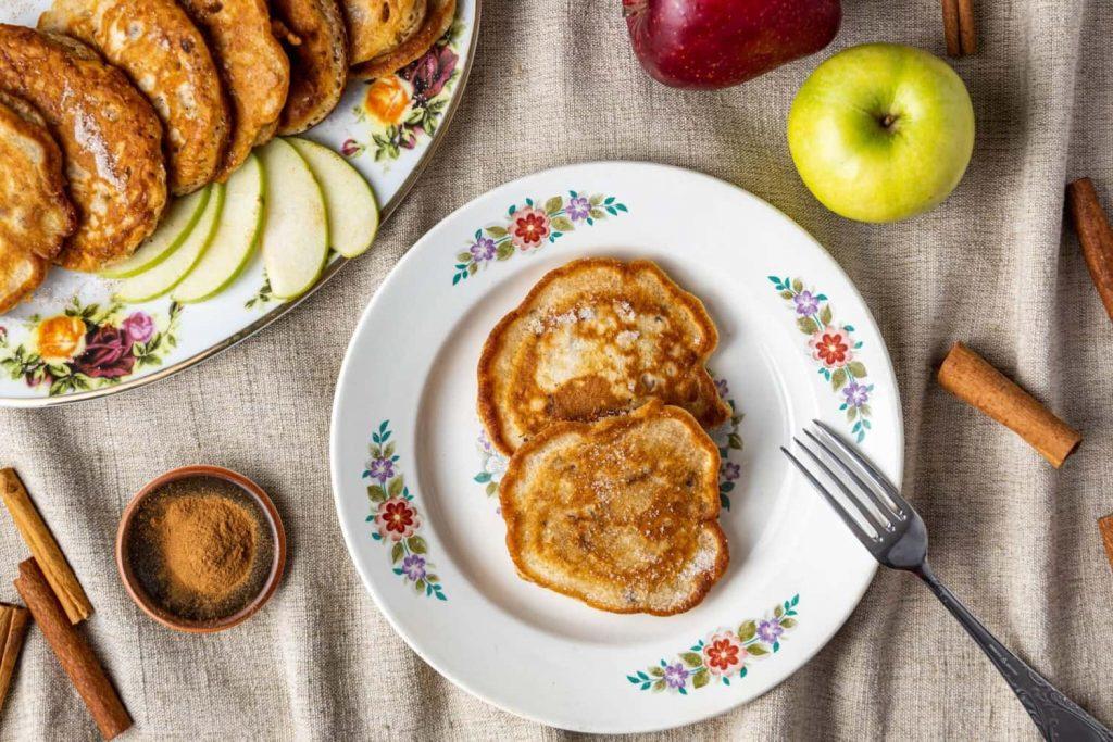 Περιχύνουμε τις τηγανίτες μήλου, γαρνίροντας με φρέσκα φρούτα.