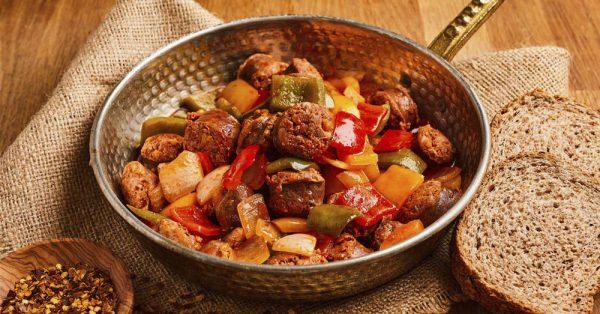 παραδοσιακό σπετσοφάι με πολύχρωμες πιπεριές και λουκάνικα σε βαθύ τηγάνι και δίπλα δύο φέτες ψωμί